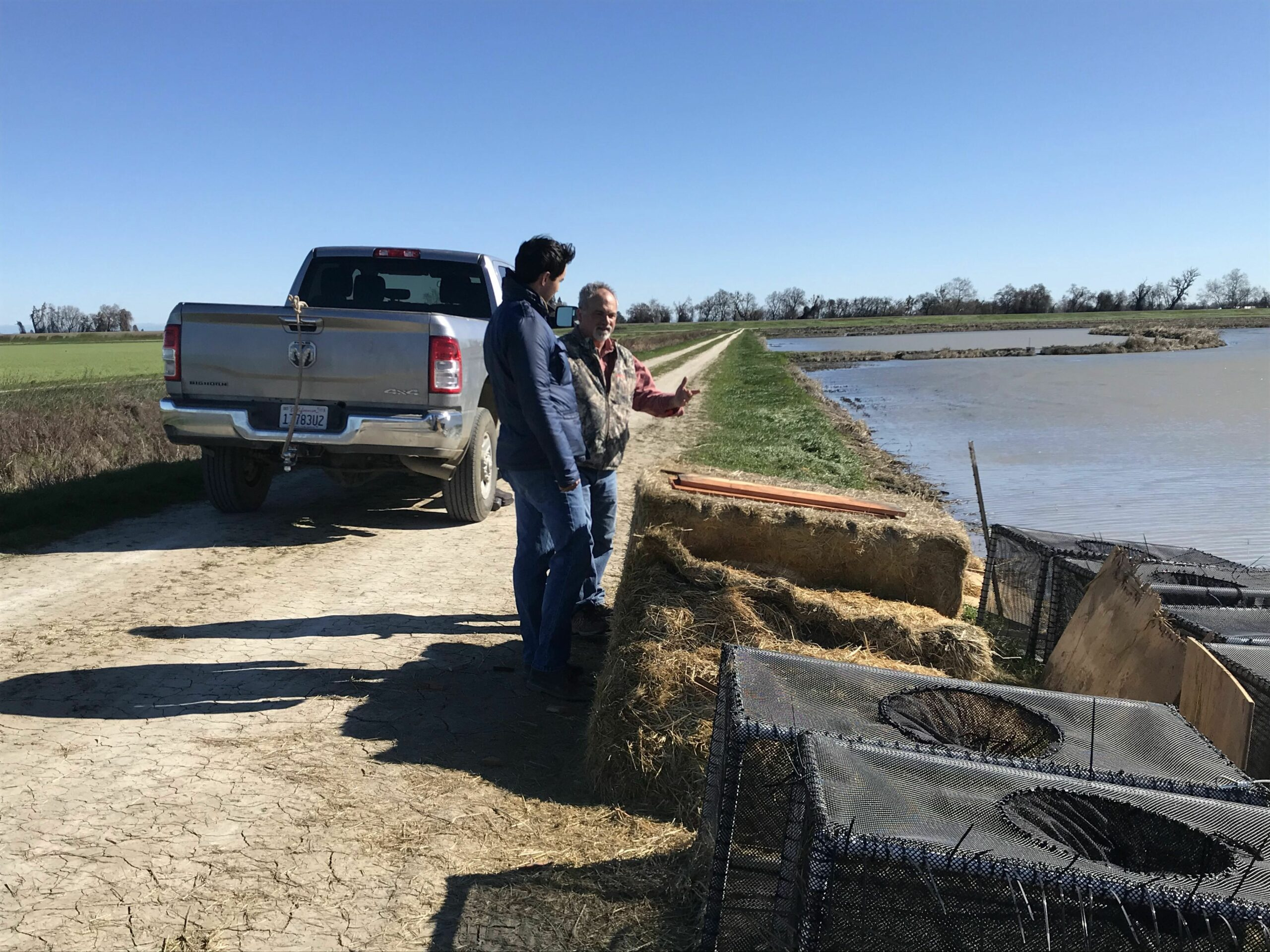 Ben Sacher, State Affairs Manager for Syngenta Crop Protection. LLC, discussing the fish cage design with Paul Buttner, CRC's Salmon Pilot Project Manager.